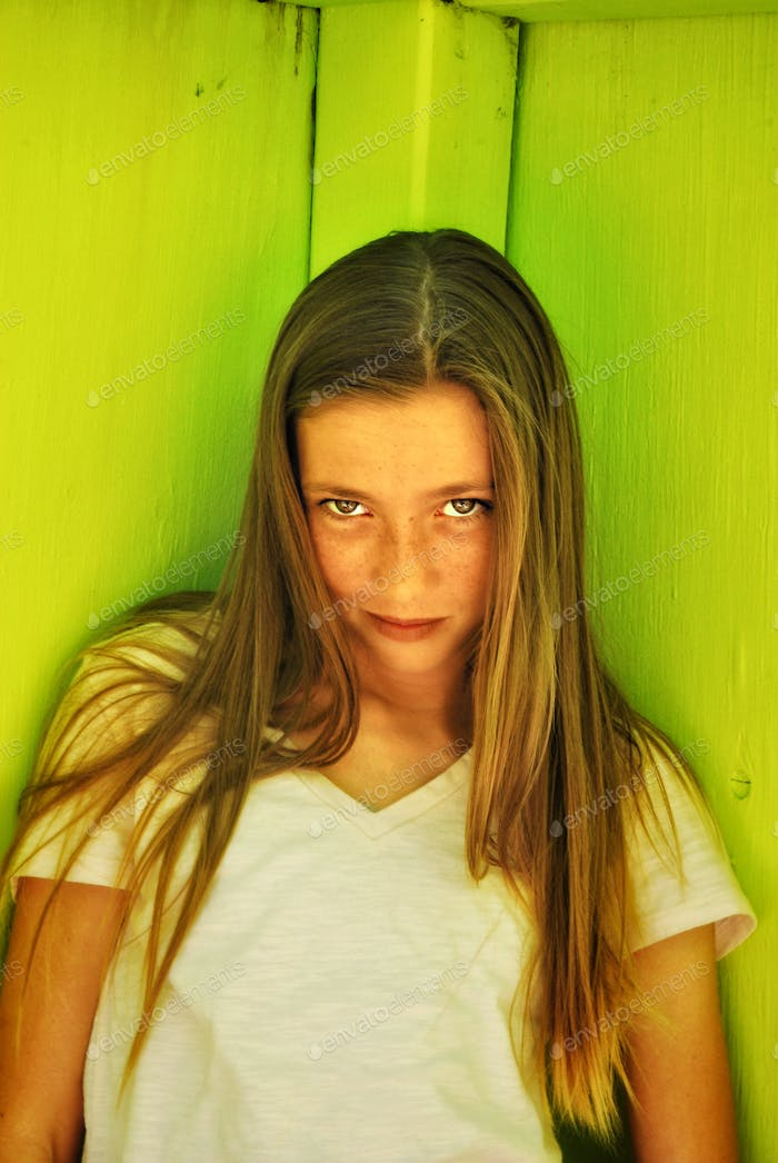 Portrait of young girl in front of a green wall.