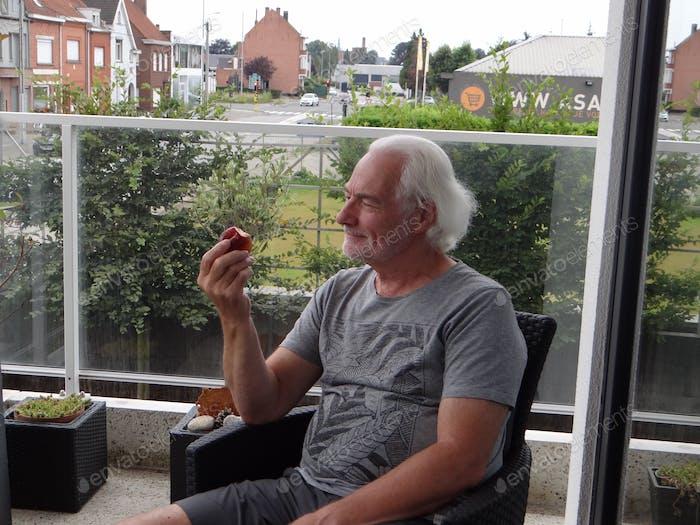 Elderly man sitting on his terrace eating a peach