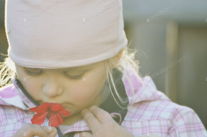 Urban kid found a flower on a October day