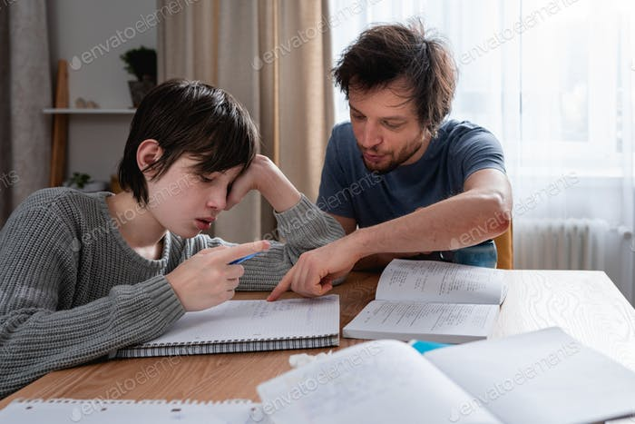 Teenager boy doing school lessons at home. Dad helping solve difficult math problems