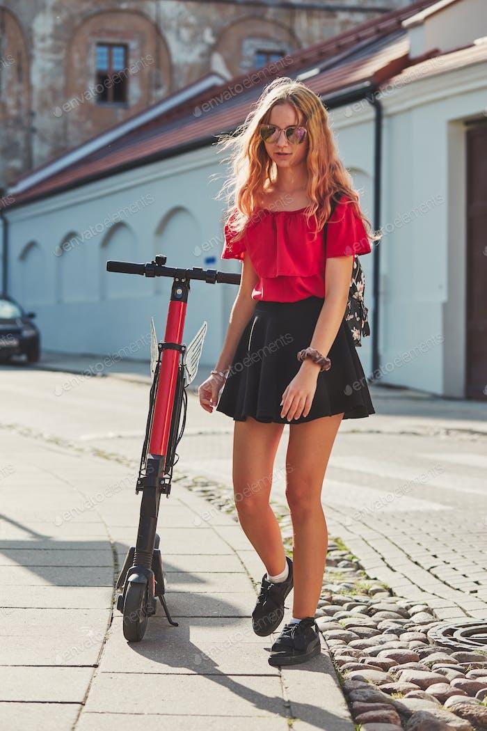 Mädchen mit Elektro-Scooter auf der Straße in der Innenstadt gemietet mit Service auf dem Smartphone