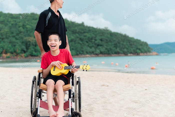 Asian special child on wheelchair is playing yellow ukulele happily on the beach