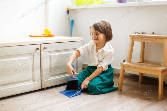 kid girl in linen apron sweeps the floor with a brush and a dustpan