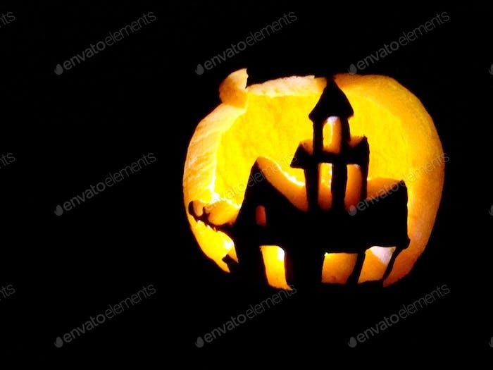 A haunted house cutout in a jack-o-lantern pumpkin for Halloween.