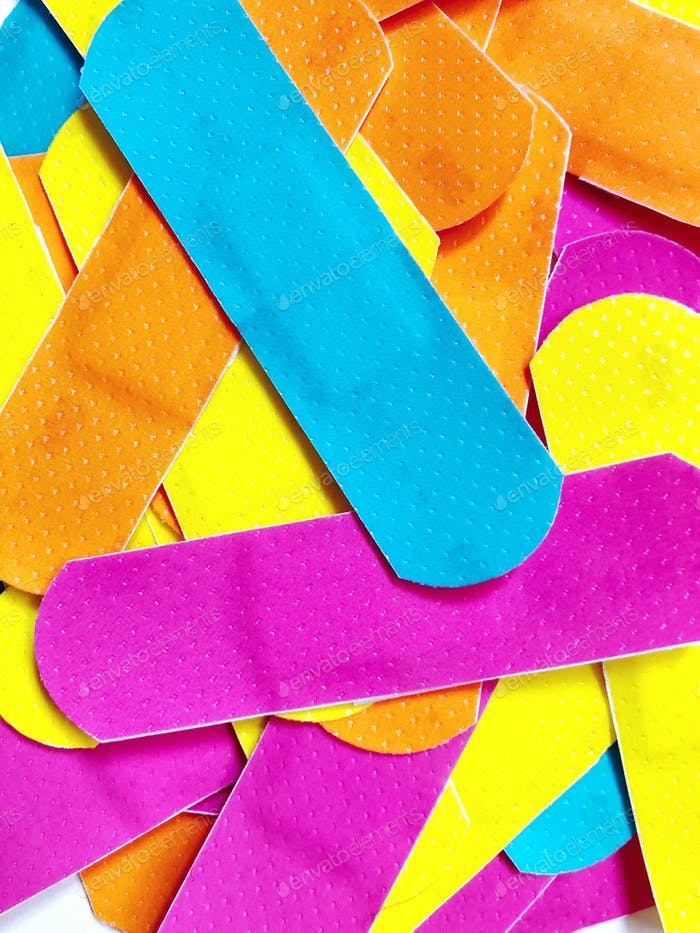 Bright and bold colors. Vibrant and colorful bandages (sticking plasters). First-Aid.