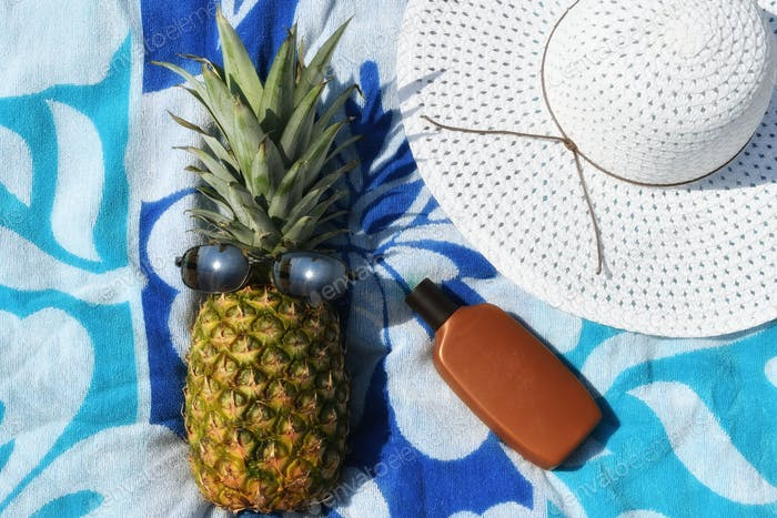 Summer Fun! A fresh green pineapple wearing sunglasses laying on a blue beach towel sunbathing with