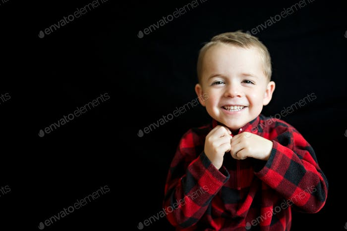 Cute preschool aged boy wearing a winter red plaid jacket and smiling and laughing