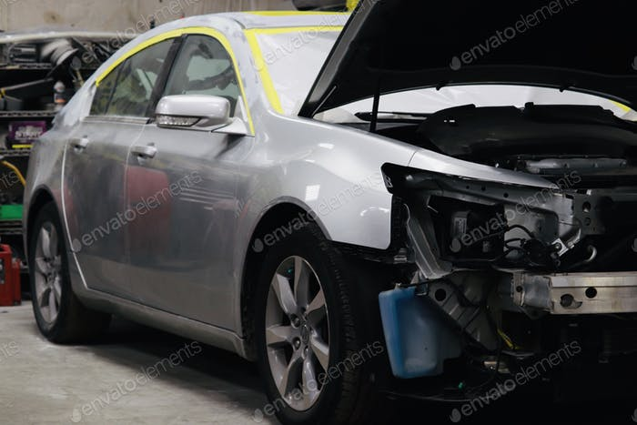 Car repair of an automobile in progress at a collision repair body shop.