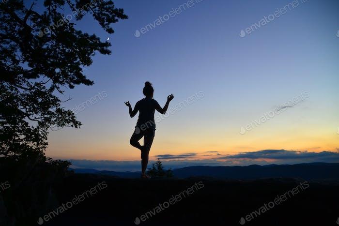 Halten Sie eine Yoga-Pose, während Sie beobachten, wie der Sonnenuntergang und der Mond herauskommen - Kopierraum