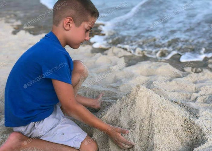 Little boy makes a pile of sand while playing at the beach