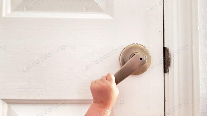 Little child's hand opening door