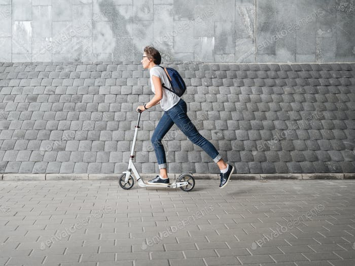 Woman rides kick scooter pass grey wall. Healthy lifestyle. Eco-friendly urban transport.