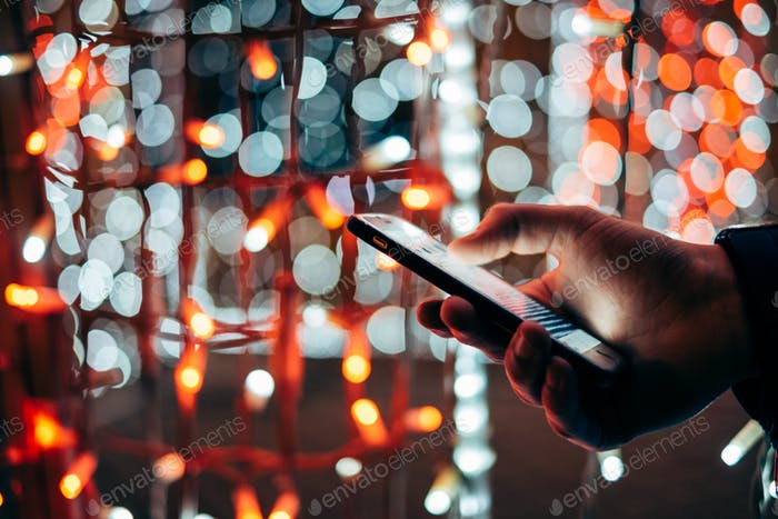 Man using mobile device at colorful light background