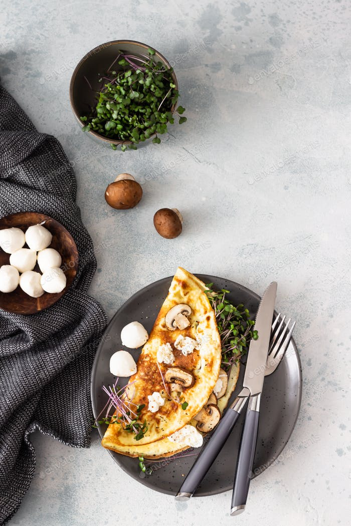 Homemade omelette with mushroom, mozzarella and microgreens on plate over light concrete background
