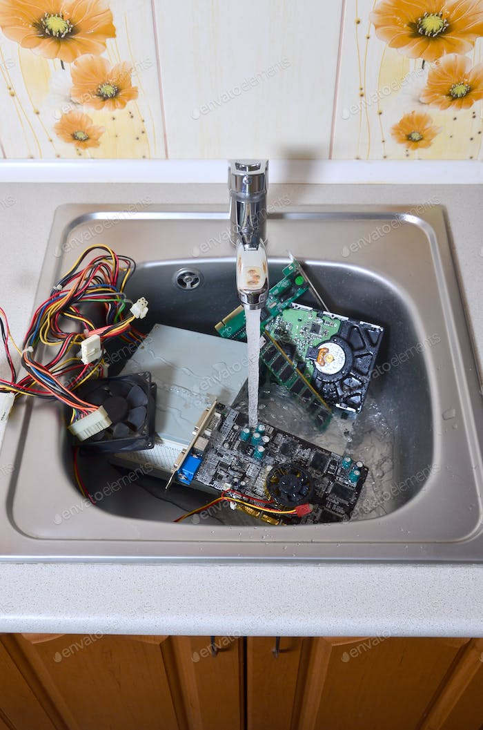 Personal computer cleaning metaphoric concept. Hardware in kitchen sink under the water flow