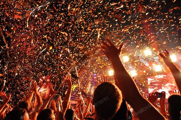 Glückliche Menschenmenge bei einem Musikkonzert hebt die Hände mit einer Serpentine hoch