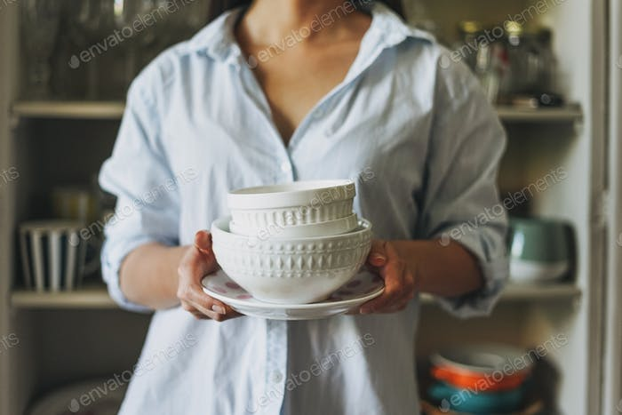 Crop photo of young woman in casual shirt with dishes near vintage sideboard at home