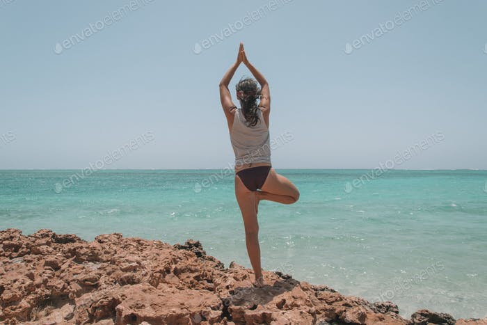Millenial doing yoga with a beach view and a pristine ocean