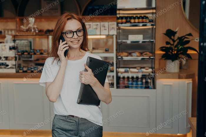 Woman entrepreneur with ginger hair has telephone conversation holds laptop