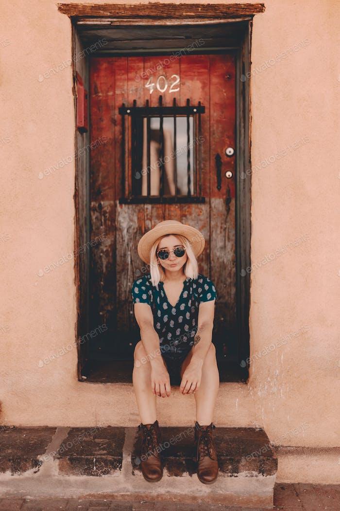 Woman is sitting near old wooden door
