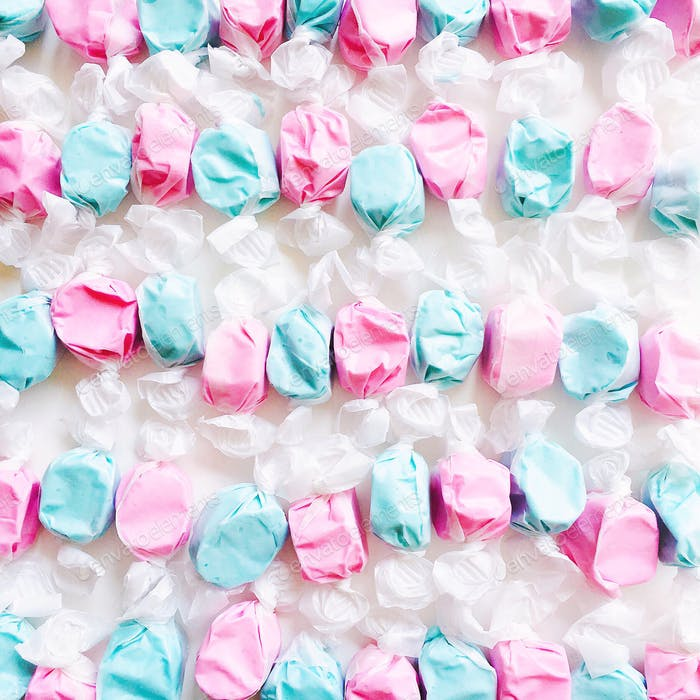 Neatly lined rows of wrapped alternating pattern pink and blue taffy candy on a white background.
