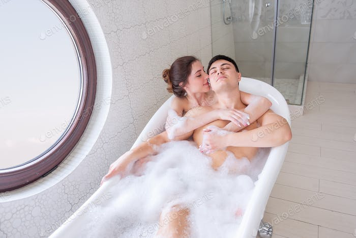 A loving couple takes a bubble bath in a minimalist white, modern interior. Young girl hugs a man