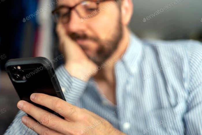 Скучающий человек прокручивается на своем смартфоне