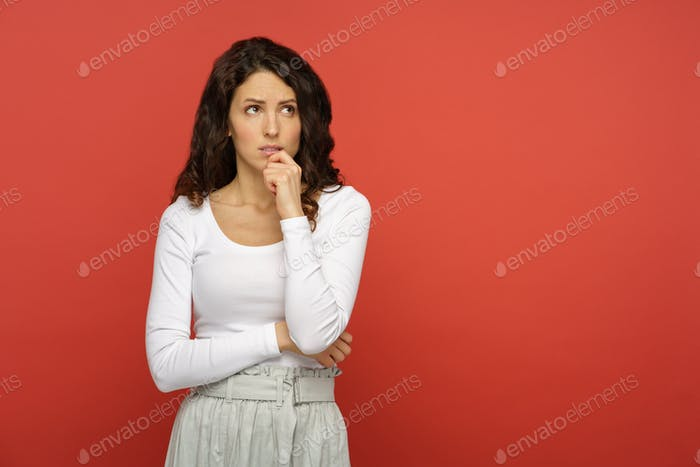 Serious doubtful woman look up think pensive confused. Young girl concerned upset bite lip in doubts