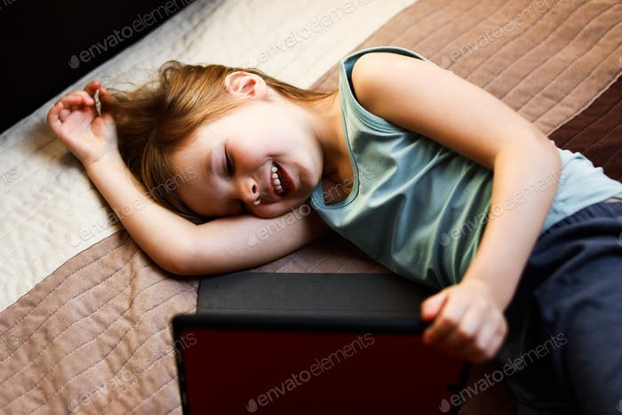 toddler girl with tablet on the bed