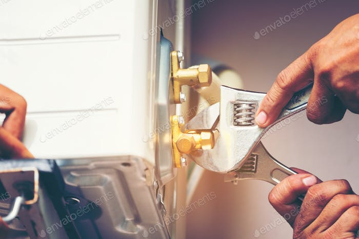 Technician hand using fix wrench to tighten outdoor unit of air condition