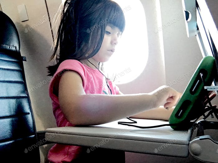 Toddler travel - kids using a mobile device on the plane