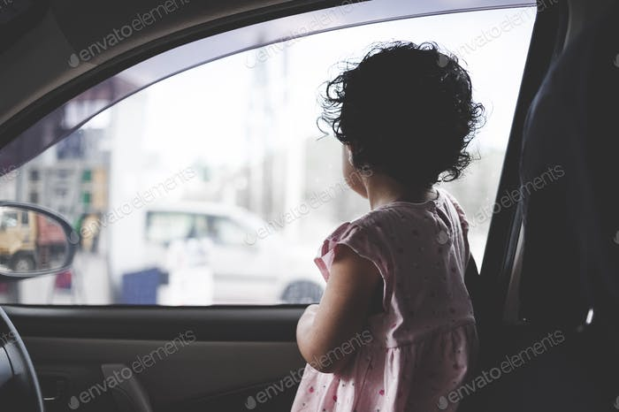 Kid looking through window waiting for her parent to come back.