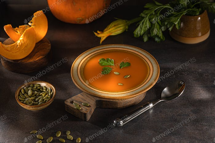 Pumpkin soup with cream on a dark background is a healthy food concept