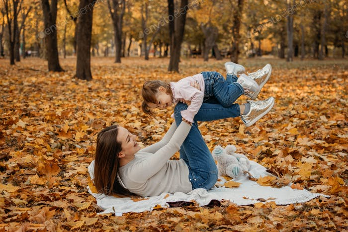 Happy family mom and toddler baby girl playing outdoors in fall park. Little girl and her mother