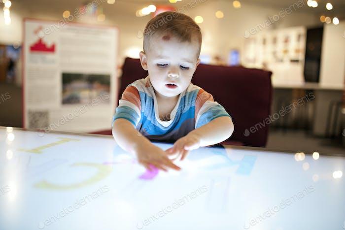Kleinkind spielt und buchstabiert auf einem riesigen Surface-Pro-Touchscreen