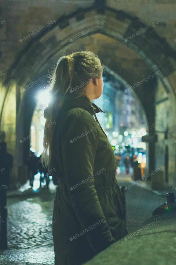 Girl looking through a city arch to see a brightly lit street in the background at night