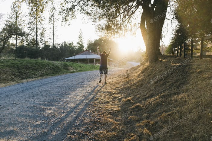 Man walking triumphantly with arms raised along country dirt road during golden sunset