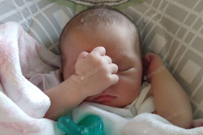 Cute little baby infant with chubby cheeks sleeping, napping with her hand fist covering her face