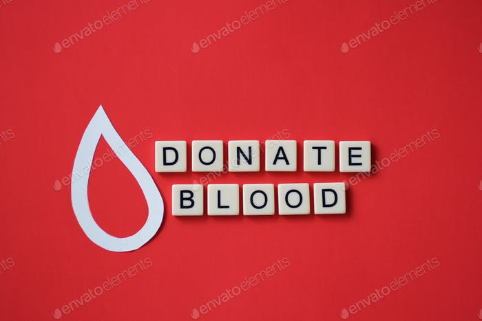 """Overhead of tiles with """"Donate blood"""" phrase spelled on red background."""