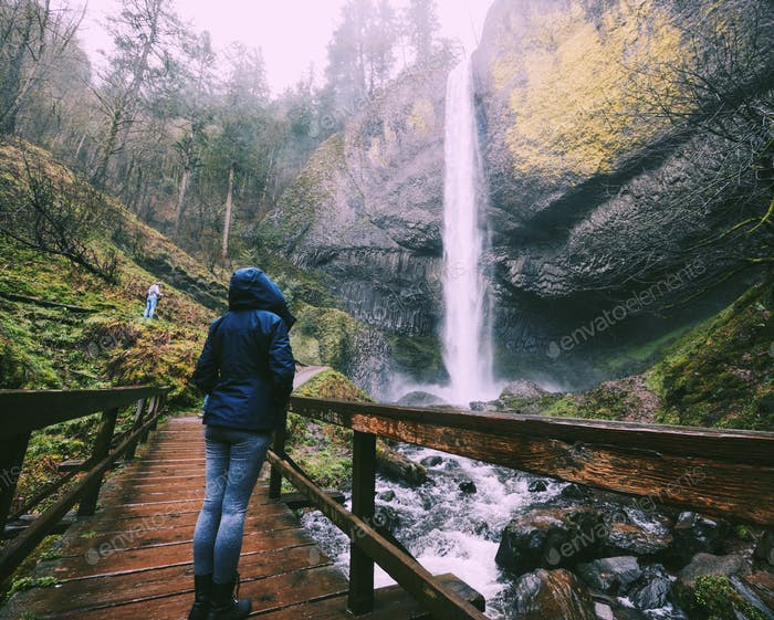 Woman in hooded rain jacket standing in forest looking at large waterfall from bridge over water
