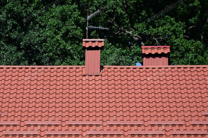 High quality red metal tile roof of a house against green trees background