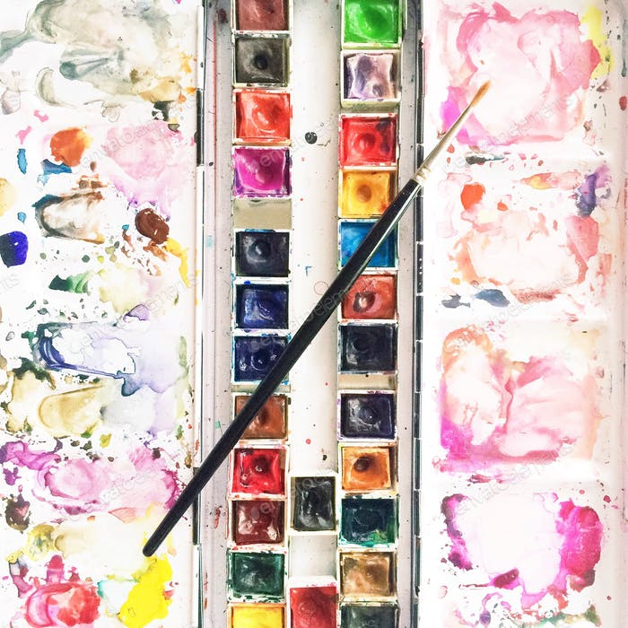 Well-loved colorful watercolor paint palette travel kit with paintbrush.