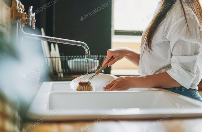 Young woman washes dishes with wooden brush with natural bristles at the window in kitchen