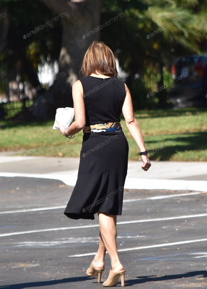 Dressed up business woman in black with a clutch purse