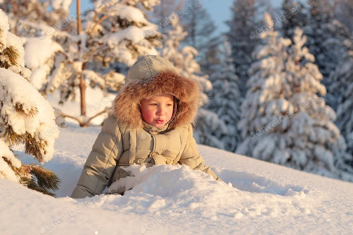 Cute little boy are playing with snow in snowdrift.