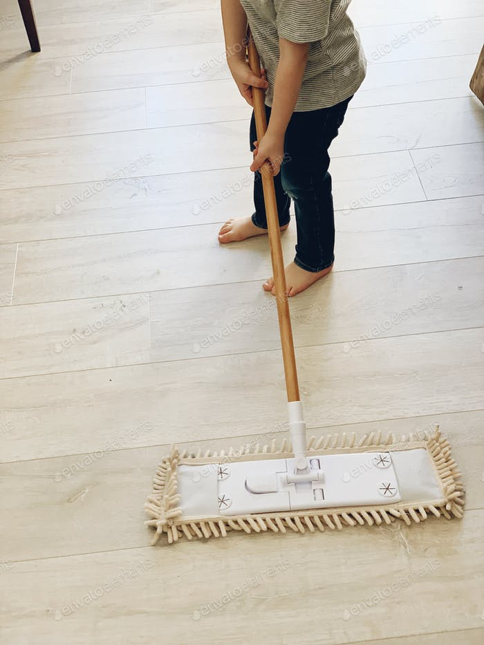 Toddler holding a broom and sweeping the floor