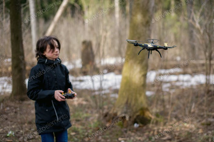 Teenage boy launches drone outdoors