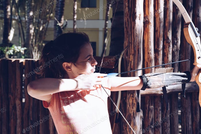 A young girl practicing archery, aiming at a target with a bow and arrow  💲 ✨NOMINATED✨