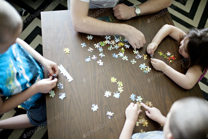 family doing a puzzle together around the table at home