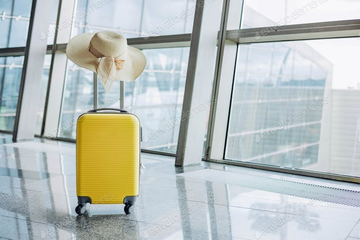 Yellow suitcase and woman straw hat in airport departure lounge on airplane background.